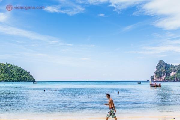 Onde ficar em Koh Phi Phi: A praia de Loh Dalum, a mais popular da ilha de Koh Phi Phi com suas águas azuis, paredes de rochas verdes. O céu está azul. Um homem anda na areia em frente a água.