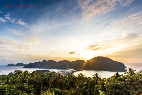 Onde ficar em Koh Phi Phi: Koh Phi Phi vista do alto do mirante da ilha, durante o pôr do sol, com o céu azul e o sol alaranjado. Muito verde em primeiro plano.