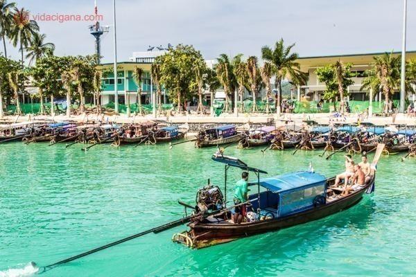 Onde ficar em Koh Phi Phi: Tonsai Pier em Koh Phi Phi, por onde chegam os barcos do continente na Ilha, com suas águas verdíssimas e transparentes. Vários longtail boat estão ancorados na orla do pier.