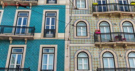Onde ficar em Lisboa: Os famosos sobrados em Lisboa, com suas fachadas feitas em azulejos. Na foto são dois prédios, um dos lado do outro, com azulejos diferentes. Várias janelas dão para a rua, com sacadas. É uma arquitetura bem agradável e bonita.