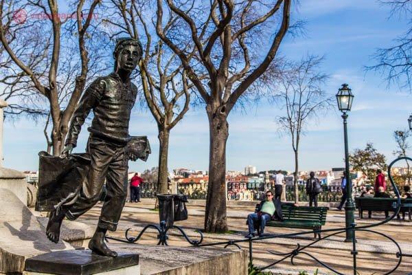Onde ficar em Lisboa: O Miradouro de São Pedro de Alcântara fica no Bairro Alto de Lisboa, uma das áreas mais badaladas da cidade. Aqui vemos uma estátua de um menino carteiro. Ao longe o mirante, com várias pessoas vendo a cidade ao longe. O céu está azul, as árvores estão sem folhas, pois é inverno.