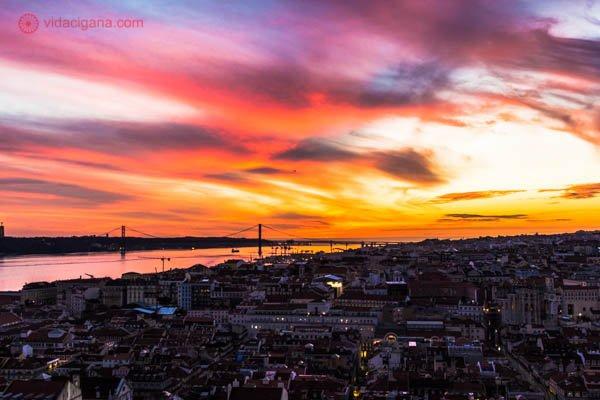 Onde ficar em Lisboa: A vista do alto do Castelo de São Jorge, em Lisboa, um dos melhores lugares para se ter uma vista privilegiada da cidade. Na foto vemos toda a cidade lá embaixo durante o pôr do sol, que vai das cores amarela até o roxo, simplesmente lindíssimo!