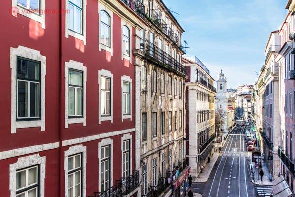 Onde ficar em Lisboa: O Cais do Sodré é uma nova área para se hospedar em Lisboa. Cheia de sobrados incríveis, de várias cores e pertinho da estação de trem que leva a Belém e Cascais. Na foto passamos pela rua de cima, onde é possível ver o trilho do eléctrico. O céu está azul.
