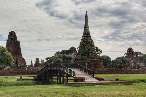 O enorme sítio arqueológico de Ayutthaya na Tailândia, com suas muitas pontes, gramados verdes e ruínas por todos os lados.