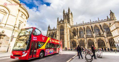 O que fazer em Bath: Bath é uma cidade perfeita para caminhar, sendo fácil ir de um ponto turístico a outro. Na foto vemos um ônibus turístico vermelho passando na frente da Bath Abbey, a igreja mais famosa da cidade. O céu está azul, com nuvens brancas, em um dia ensolarado.