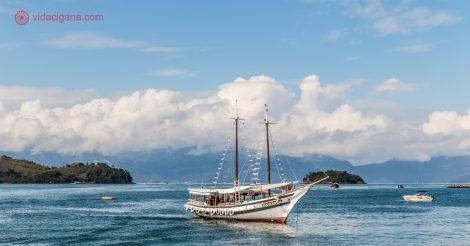 Passeios em Angra dos Reis: Uma escuna parada na Baía de Angra, cercada pela serra e por infinitas ilhas.