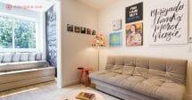 Airbnb no Rio de Janeiro, uma linda sala com um sofá cinza, vários quadros acima do sofá, uma luminária colorida, e um sofá no beiral da janela, cheio de verde lá fora