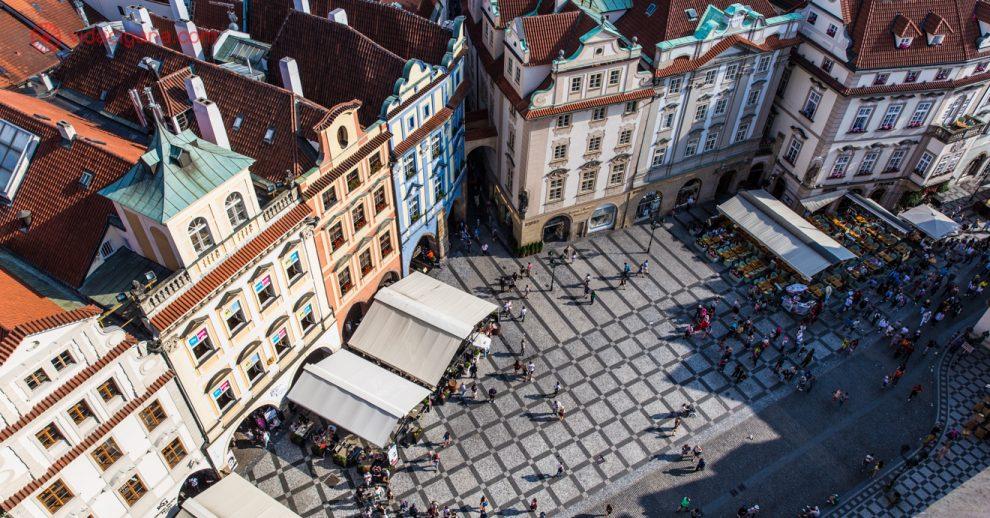 Onde ficar em Praga: A Cidade Velha vista do alto da Torre do Relógio. Chão de piso quadriculado cinza claro e escuro, casinhas antigas de 4 andares de diversas cores, e muitos turistas transitando pela pequena praça que tem em frente