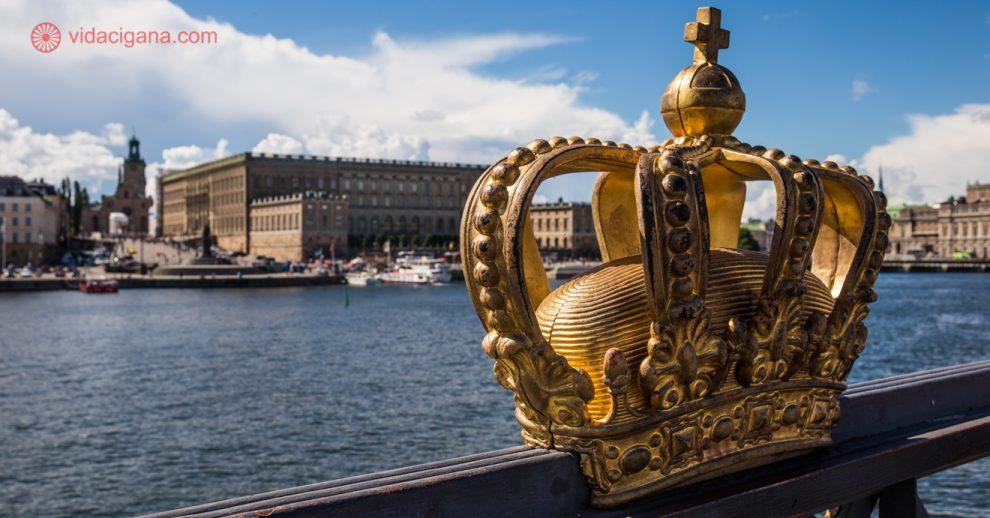 O que fazer em Estocolmo: A Ponte Skeppsholm em primeiro plano, com sua estrutura metálica e uma coroa dourada em seu gradil, com o Palácio de Estocolmo em seu fundo. O céu está azul, com nuvens brancas. Entre a ponte e o palácio fica o mar.