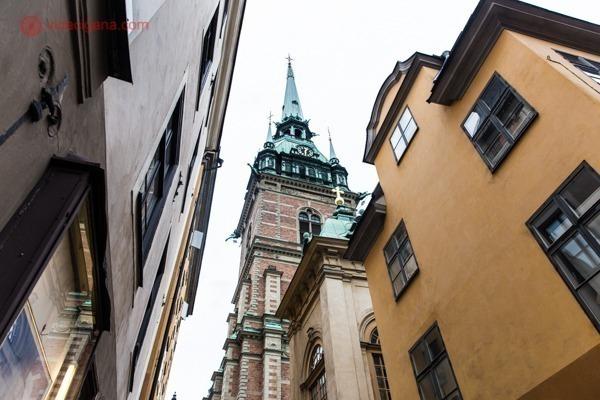 O que fazer em Estocolmo: A Catedral de Gamla Stan, em Estocolmo, com sua torre verde, prédios terrosos em volta. A igreja fica bem apertada entre outros prédios antigos.