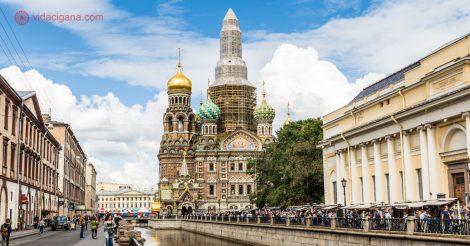 Onde ficar em São Petersburgo: A lindíssima Igreja do Sangue Derramado, em São Petersburgo, na beira de um dos vários canais na cidade, com várias cúpulas diferentes, algumas douradas, outras revestidas em mosaicos verdes, amarelos e azuis. Sua torre principal está em reformas, coberta por tecidos de obra. Muitas pessoas estão ao redor da igreja e na margem do rio, que é gradeada. O céu está azul com nuvens brancas