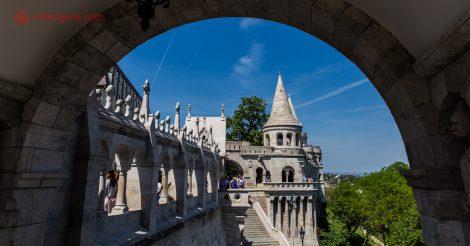 Roteiro Praga Viena Budapeste: O Fisherman's Bastion, em Budapeste, visto do interior de um arco, com suas torres pontudas e céu azul.