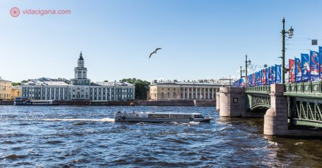 O que fazer em São Petersburgo: A margem do Rio Neva, com um barco passando por baixo da Ponte do Palácio, repleta de bandeiras da Copa do Mundo 2018. Do outro lado da margem, o museu Kunstkamera, com suas paredes verdes. O céu está azul e uma gaivota voa no céu.