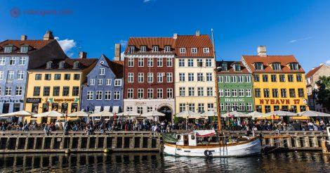 Onde ficar em Copenhague: O famoso porto de Copenhague, repleto de casinhas coloridas na beira do mar, com barcos ancorados. O céu está azul. Várias pessoas almoçam na beira do mar, na frente das casinhas coloridas.