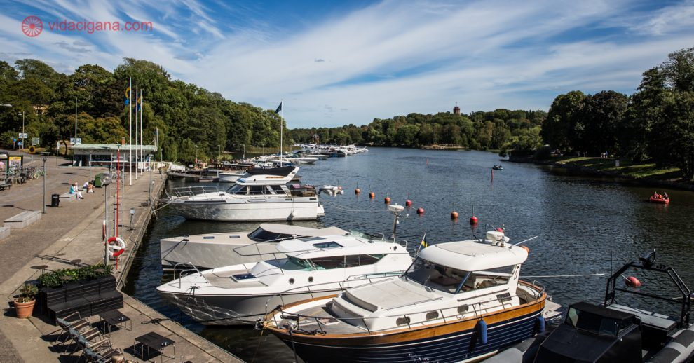 Onde ficar em Estocolmo: lindos barquinhos na orla de Estocolmo durante o verão, com o mar azul, vegetação verde e o céu com algumas nuvens brancas