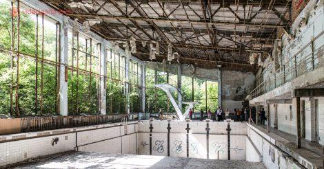 Como visitar Chernobyl: A Piscina Pública Lazurny, vazia e abandonada, com seus azulejos descascados e pichados. O trampolim na ponta com duas alturas diferentes. O teto danificado, as janelas quebradas, com a mata adentrando o espaço