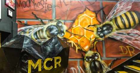 O que fazer em Manchester: Uma parede com um mural pintado, cheio de abelgas em uma comeia, representando o povo de Manchester.