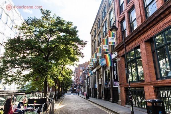 Vista da Canal Street com as fachadas do edifícios decoradas com bandeiras do arco-íris