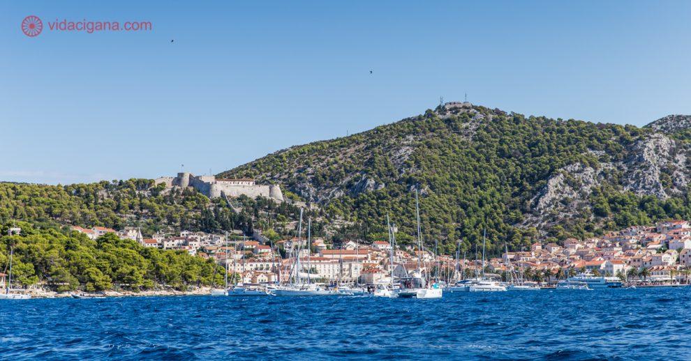 Passeio de barco em Hvar: a cidade de Hvar vista do barco, com seu porto cheio de barcos e lancha, com suas casinhas nos pés da montanha, de telhados terracota. A montanha tem o castelo da cidade, cercado de verde.