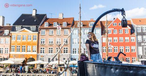 O que fazer em Copenhague: uma mulher na proa de um barco aportado no porto de Nyhavn, a região mais famosa de Copenhague