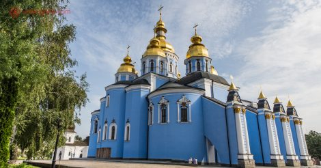 O que fazer em Kiev: A Catedral de São Miguel das Cúpulas Douradas, com suas paredes azuis, cúpulas douradas, num pátio com árvores e céu azul