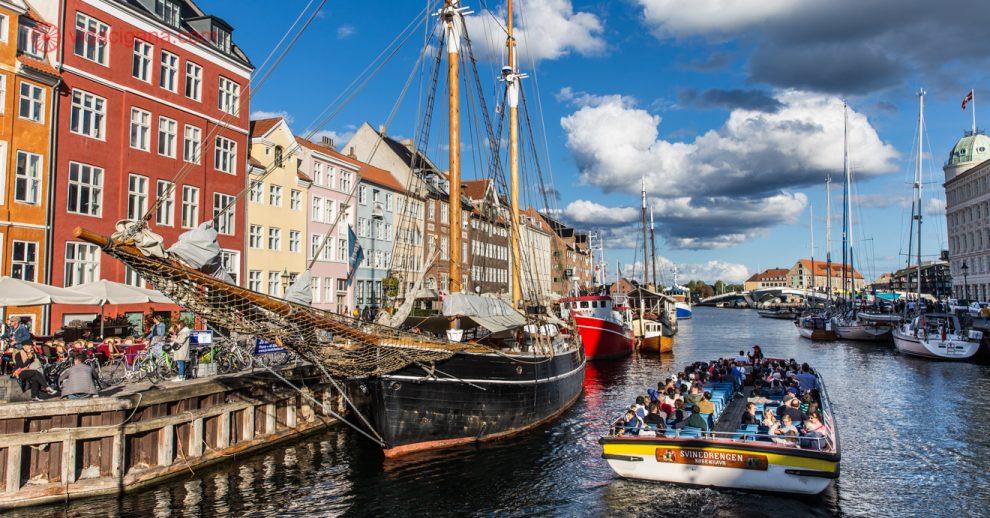 Passeio de barco em copenhague: O porto de Nyhavn, com suas casinhas coloridas na esquerda, um barco ancorado ao lado das casinhas e um barco cheio de turistas saindo do canal