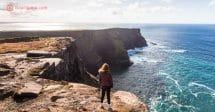 Aluguel de carro pela Irlanda: uma mulher ruiva na beira de um precipício na Irlanda, olhando o mar