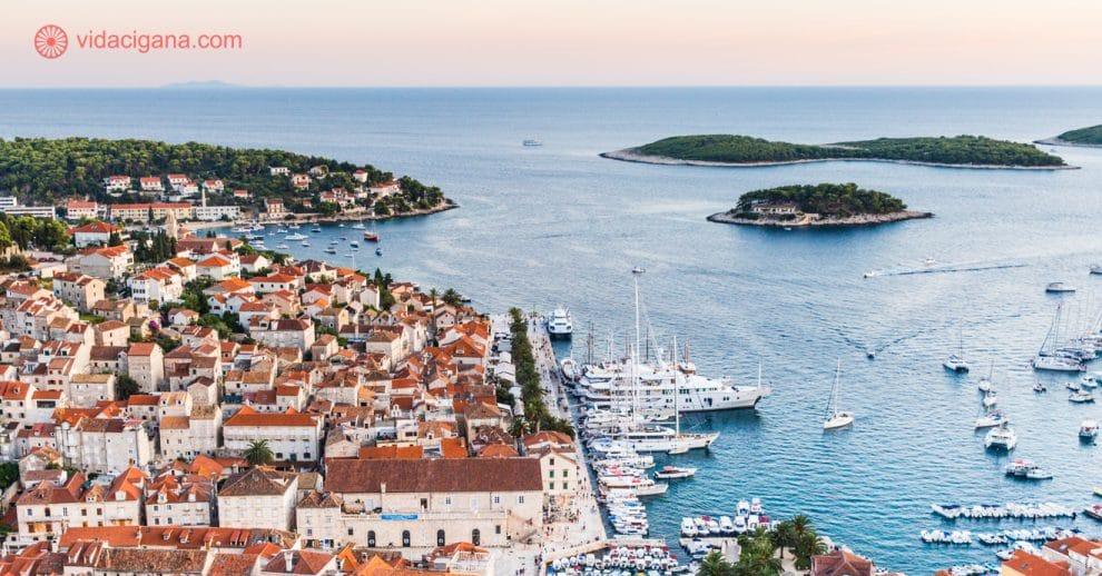 Hvar vista do alto da fortaleza da cidade, com seus telhados ocre, barcos ancorados no porto, mar azul e ilhas espalhadas. a foto foi tirada durante o pôr do sol