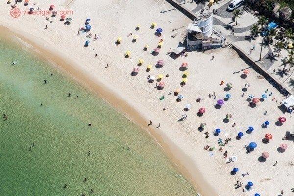 A Praia do Arpoador vista de cima, com pessoas na água e vários guarda sol abertos na areia