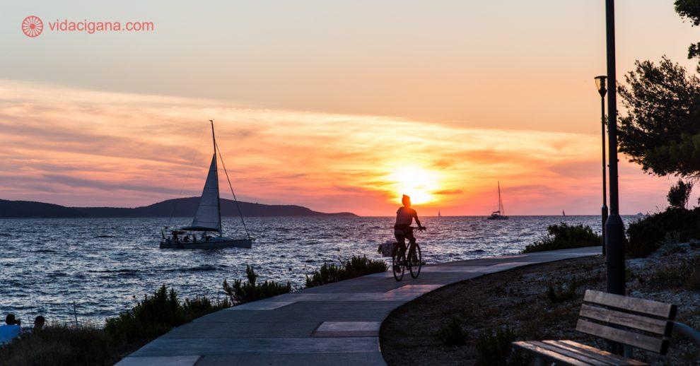 O que fazer em Hvar: uma mulher pedalando em uma bicicleta na frente do mar, na frente do sol se pondo, com um veleiro passando do lado esquerdo da foto. O céu está laranja