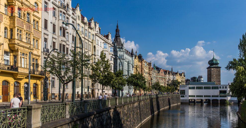 Seguro viagem europa: a cidade de Praga na beira do rio com vários prédios coloridos e árvores na beira do rio.