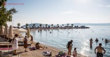 O que fazer em Split: uma praia na Croácia com várias pessoas na areia, adultos, crianças e idosos, com o mar bem calmo e com uma passarela de pedras ao fundo com palmeiras. O céu está azul e o sol brilha a contraluz