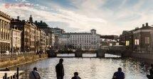 O que fazer em Gotemburgo: Pessoas sentadas nas margens do rio em Gotemburgo, na Suécia, com pontes e prédios baixos a frente
