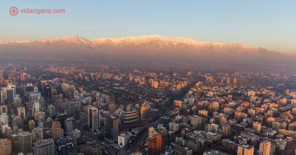 O que fazer em Santiago: Santiago vista do alto do mirante do Sky Costanera, com os prédios embaixo e a Cordilheira dos Andes cheia de neve ao fundo. A foto foi tirada durante o pôr do sol