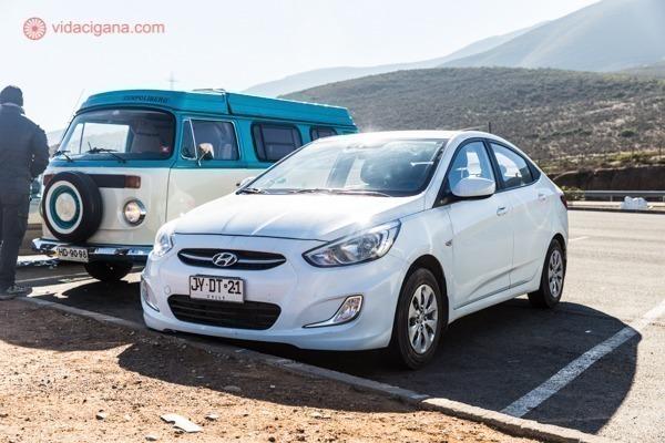 Um carro branco parado num estacionamento com uma kombi ao lado