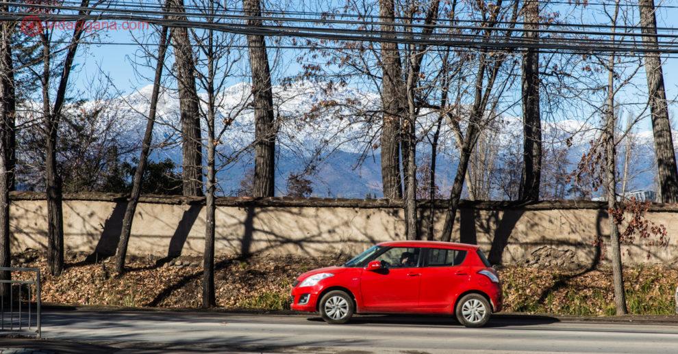 Aluguel de carro no Chile: um carro vermelho numa estrada no Chile com árvores secas atrás e a cordilheira dos andes no fundo com neve