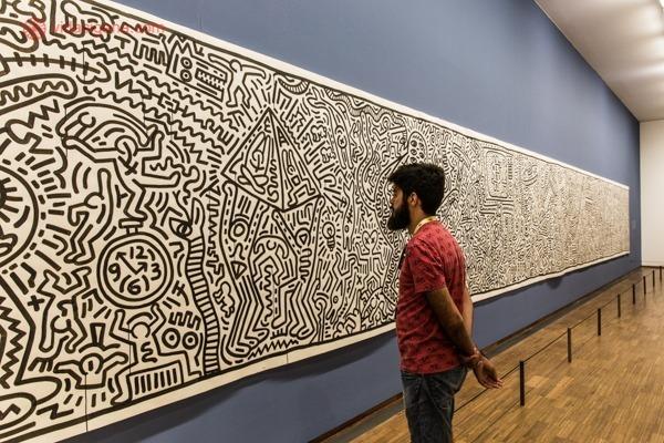 um homem olhando um quadro imenso na galeria albertina em viena