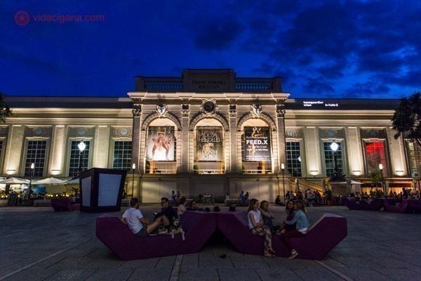 o museumsquartier, em Viena, de noite, cheio de pessoas sentadas na frente dos museus