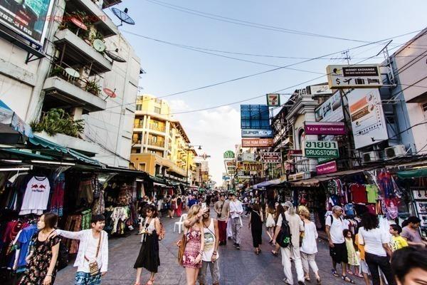 A Khaosan Road na Tailândia cheia de pedestres andando por suas ruas, com vários letreiros ao redor