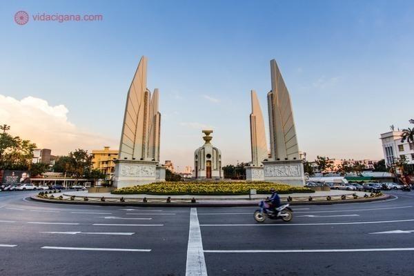 Um monumento no meio de uma rotatória na Tailândia, com uma moto andando nela