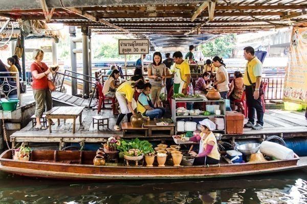 Pessoas num mercado flutuante em Bangkok