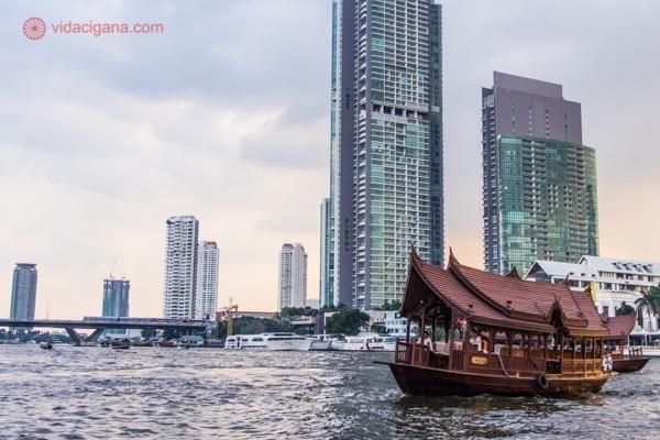 Um barco no rio chao Phraya na frente de prédios bem modernos