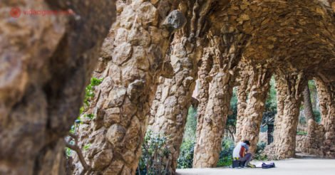 O que fazer em Barcelona: os corredores do Parc Guell feitos de pedra, com um homem tocando violão embaixo deles