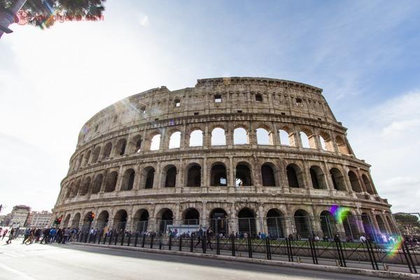 o Coliseu durante o dia com luzes do sol passando por lá