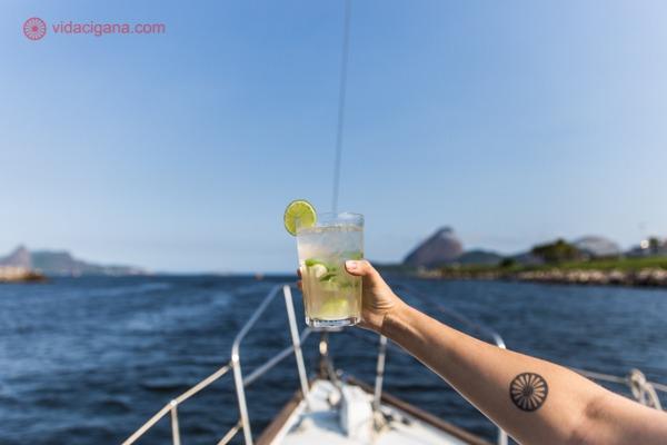 Passeio de barco pelo Rio de Janeiro: uma caipirinha sendo segurada no barco, de frente para o Pão de Açúcar