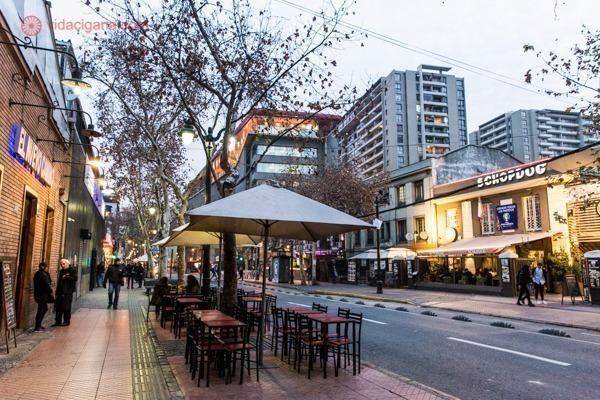Uma rua larga em Bellavista, Santiago do Chile, com várias mesas na rua, árvores peladas devido ao frio