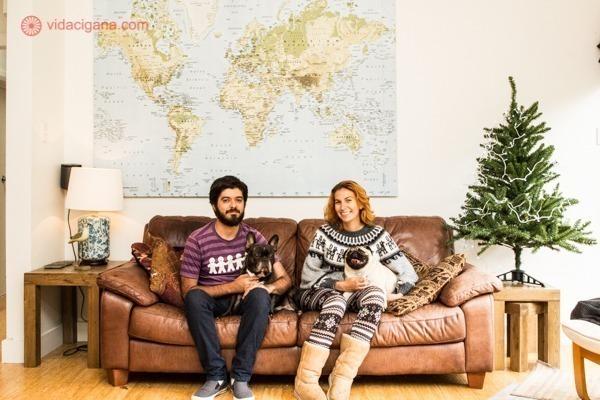 Um casal sentado com 2 cachorros num sofá