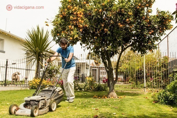 Um homem cortando a grama de uma casa