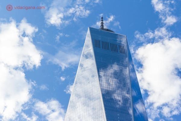 O One World Trade Center visto de baixo para cima num dia de céu azul e nuvens brancas