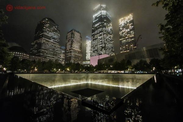O Memorial do 11 de setembro, com a piscina e os prédios ao fundo, de noite